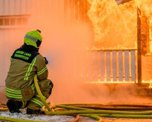 Brannmann slukker husbrann