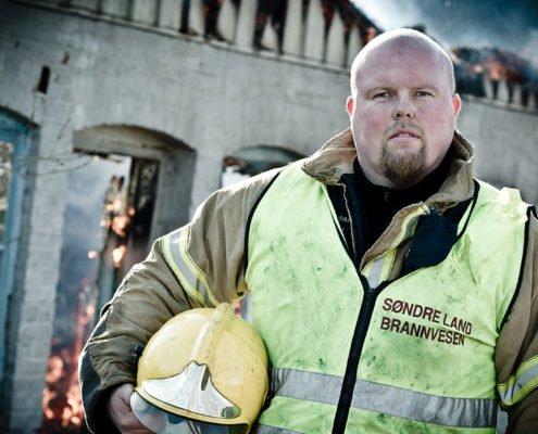Brannmann foran utbrent bygg